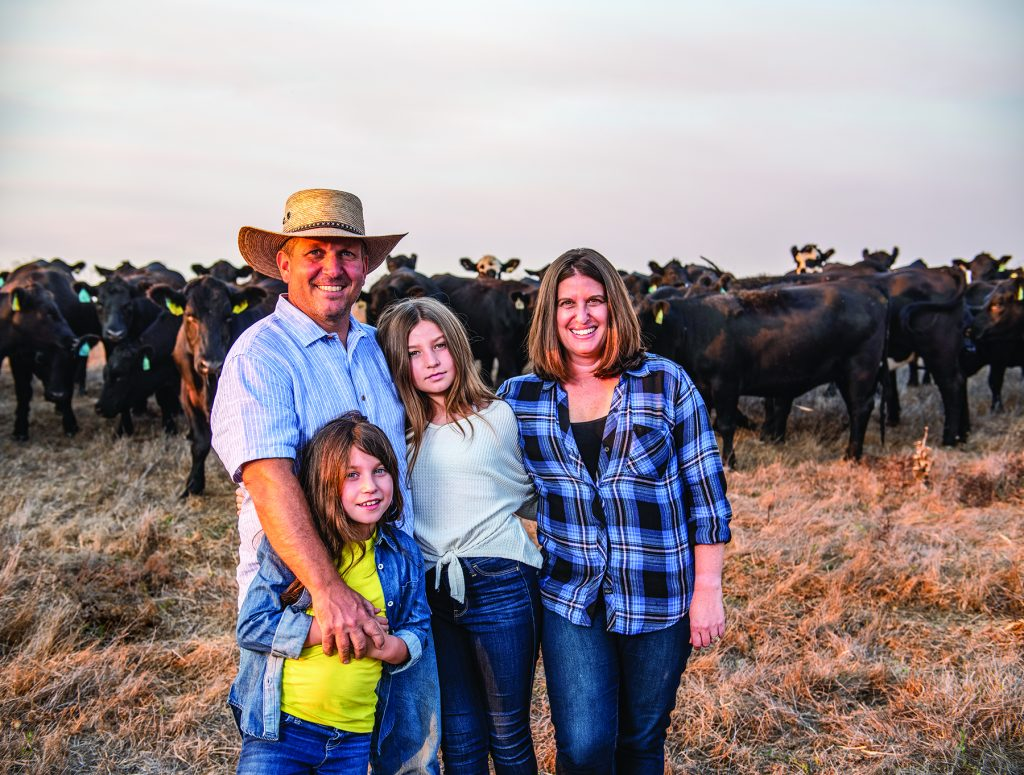 Leopold finalist and Stemple Creek owner Loren Poncia with his family, Lisa Poncia and daughters Avery (11yrs) and Julianna (8yrs) on rocks looking out over their ranch.
